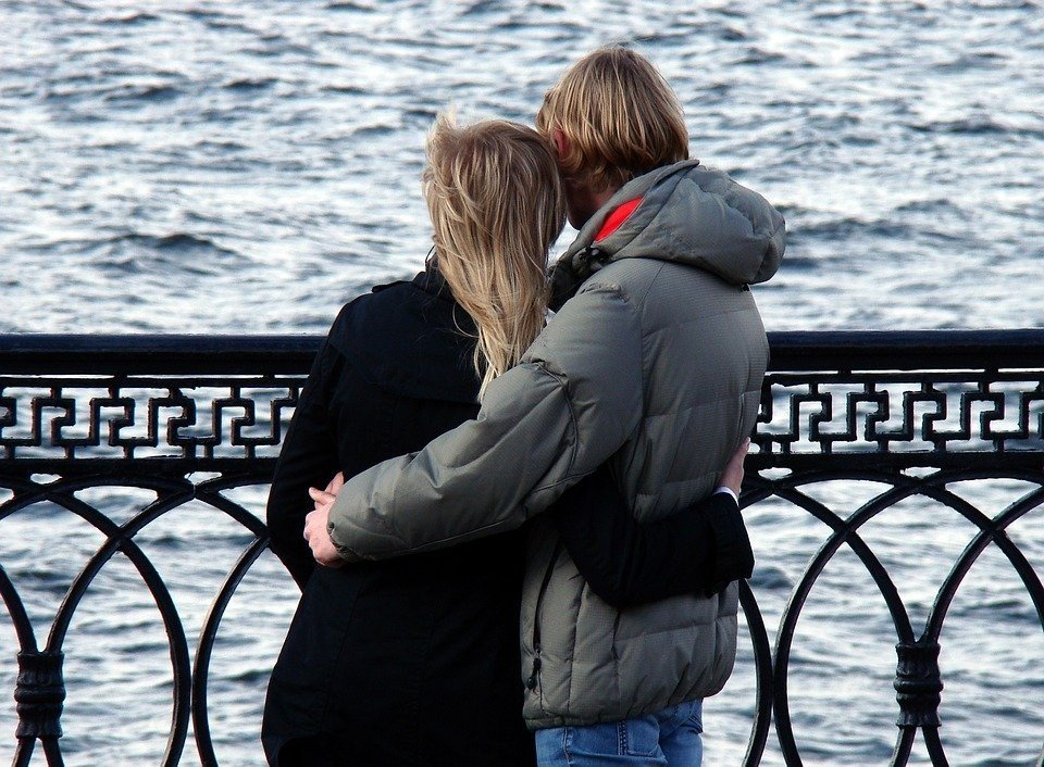 couple watching a river and holding on to each other
