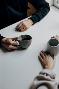 a couple communicating with coffee mugs in their hands